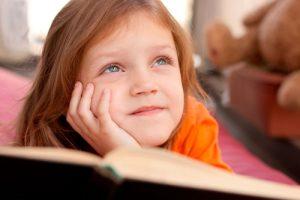 nina con libro pensando